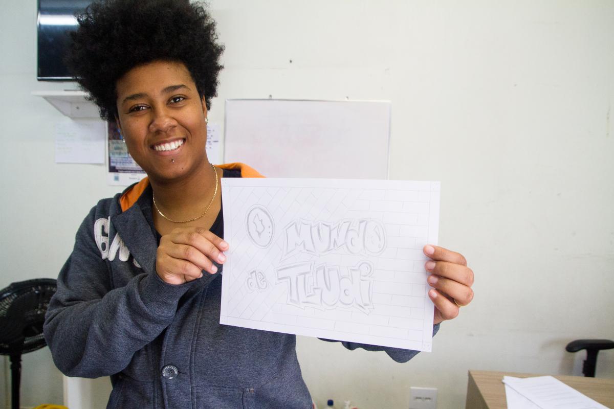 Moça segurando uma plaquinha escrito: O Mundo de Tludi